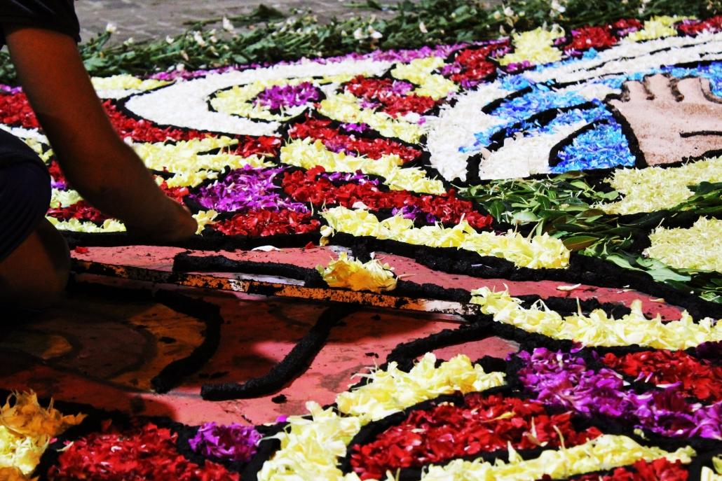 """Arte e fede, natura e cultura. Il 22 e il 23 giugno i quattro """"ingredienti"""" si incontrano e si fondono per dare vita a uno spettacolo che lascia a bocca aperta. A Montefiore dell'Aso, grazioso borgo in provincia di Ascoli Piceno, quella con l'Infiorata del Corpus Domini è una tradizione antica, che affonda le radici sul finire degli anni 30'; l'usanza è stata recuperata in chiave moderna nel 2002, diventando in poco tempo uno degli eventi più apprezzati di tutte le Marche e delle regioni limitrofe. Con alcuni particolari che la rendono unica rispetto alle analoghe manifestazioni disseminate sul territorio nazionale. In primo luogo per la lunghezza del percorso, circa 2 chilometri sui quali viene steso un immenso tappeto floreale che si articola in vari quadri, ogni anno più belli. E poi per la ricerca di materiali naturali alternativi: foglie e petali di fiori tagliuzzati, petali di fiori essiccati e macinati, ma anche essenze naturali colorate come sementi, trucioli e segature; ogni anno si sperimentano nuove essenze per ottenere risultati migliori e per offrire ai visitatori uno spettacolo unico."""